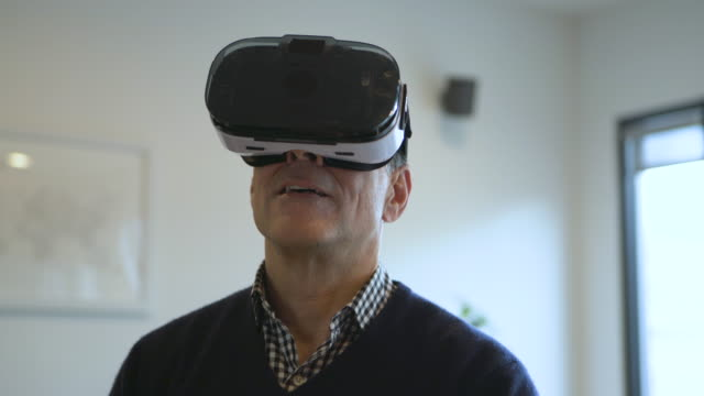 Handheld shot of man looking through virtual reality simulator while standing at home