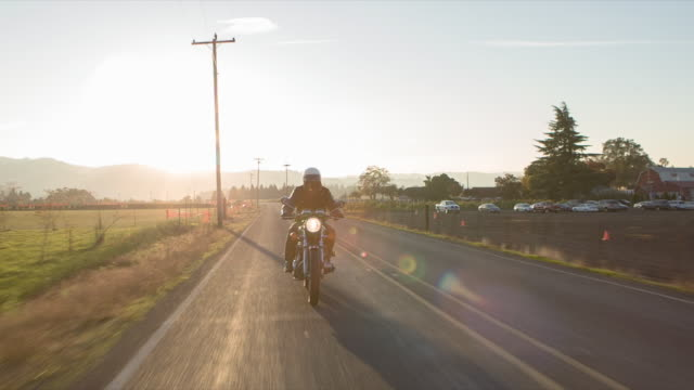Handheld shot of man riding motorcycle on road against sky during sunset