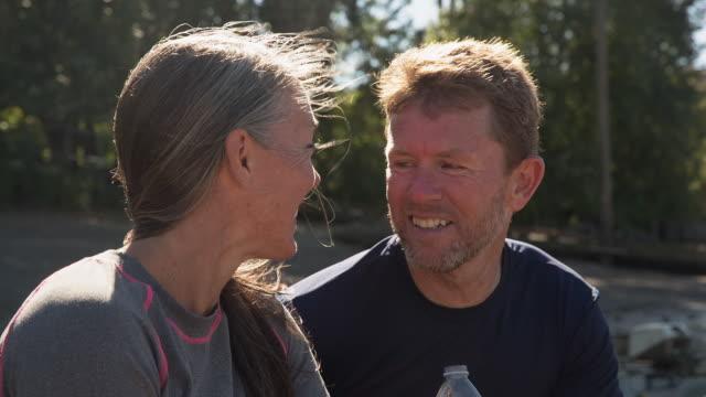 vídeos y material grabado en eventos de stock de handheld shot of mature couple talking while sitting at riverbank - barba de tres días
