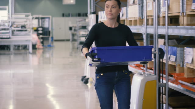 Handheld shot of mature female worker holding crate while walking by rack in warehouse