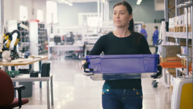 Handheld shot of mature female worker holding crate while walking in warehouse