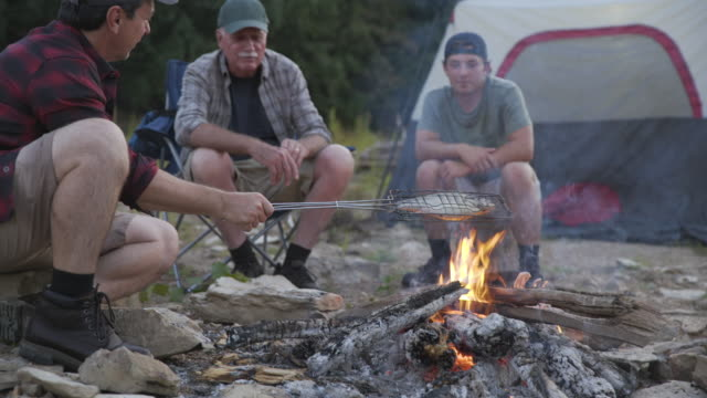 handheld shot of mature man talking to family while grilling fish at campsite - young men stock videos & royalty-free footage