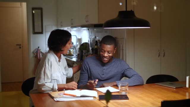 Handheld shot of mature woman cheering adopted son studying at illuminated table against kitchen