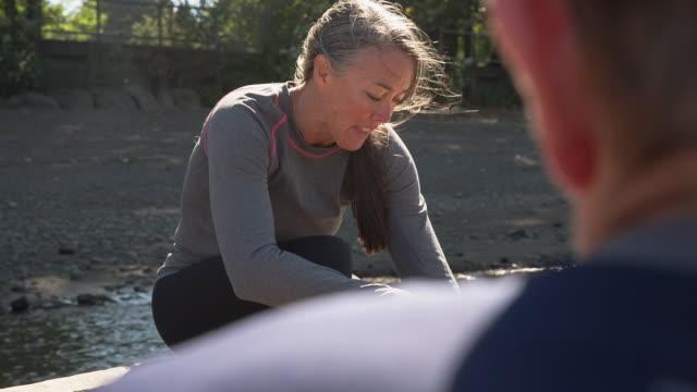handheld shot of mature woman having sandwich while talking with man on pier - 密閉点の映像素材/bロール