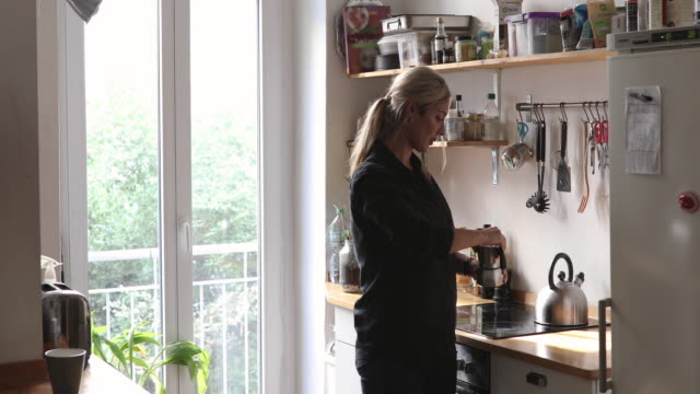 handheld shot of mid adult woman making coffee in pot at kitchen - open refrigerator stock videos & royalty-free footage
