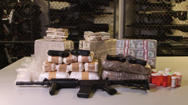 handheld shot of money, guns and drugs - still life stock videos & royalty-free footage