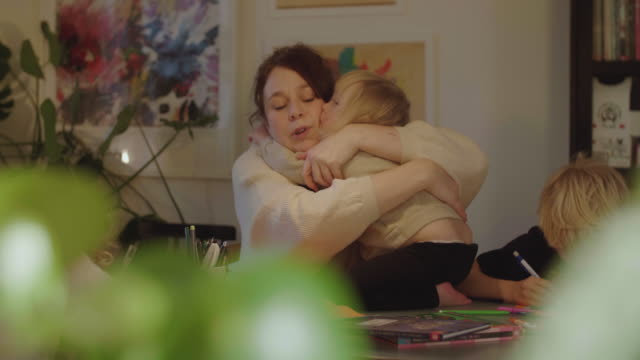 handheld shot of mother embracing disabled daughter while sitting by dining table at home - innocenza video stock e b–roll
