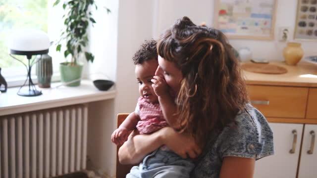 vídeos de stock, filmes e b-roll de handheld shot of mother kissing baby girl at home - carrying