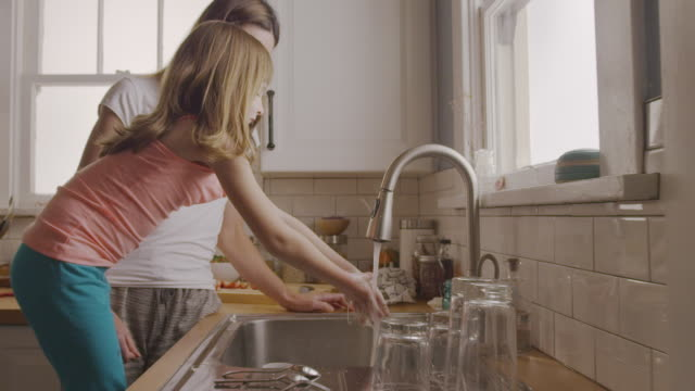 handheld shot of mother looking at daughter washing hands at kitchen sink - badrum bildbanksvideor och videomaterial från bakom kulisserna