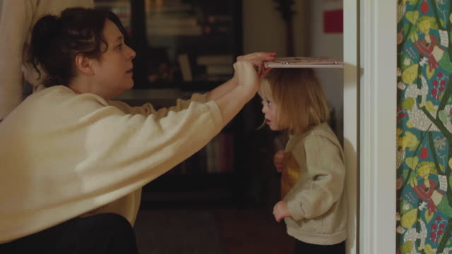handheld shot of mother measuring disabled girl's height with book at home - measuring stock videos & royalty-free footage