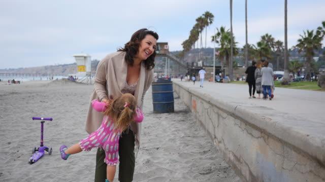 vídeos y material grabado en eventos de stock de handheld shot of mother playing with daughter at beach - cámara en mano