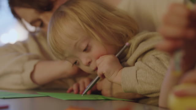 handheld shot of mother teaching disabled daughter to draw while sitting by table - differential focus stock videos & royalty-free footage