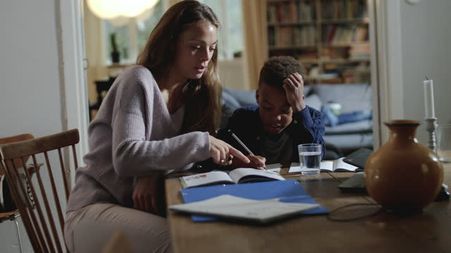 handheld shot of mother teaching while assisting son with homework at home - differential focus stock videos & royalty-free footage