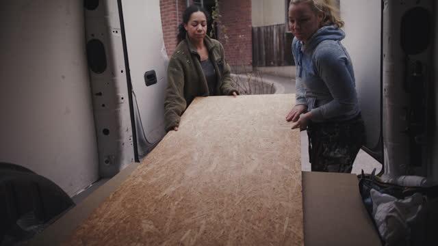vidéos et rushes de handheld shot of multi-ethnic female coworkers opening van door and unloading plank - décharger