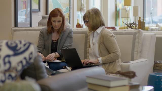 stockvideo's en b-roll-footage met handheld shot of owner using laptop computer while coworker arranging fabrics in ring binders at store - boekwinkel