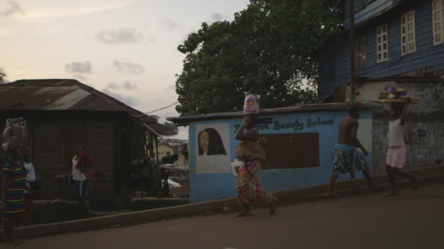 handheld shot of people walking past a beauty salon with a defaced sign at twilight in kenema, sierra leone. - sierra leone stock videos & royalty-free footage
