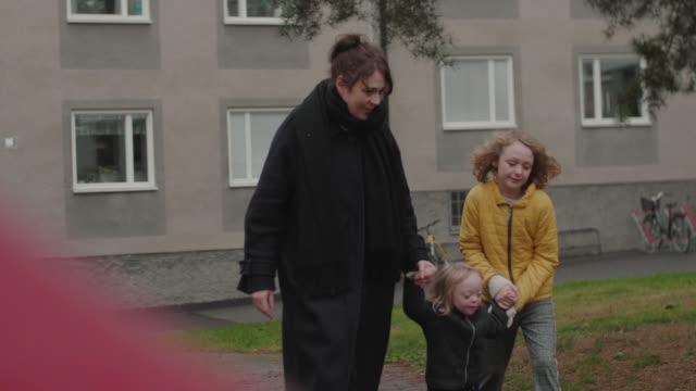 handheld shot of playful family walking on footpath against building during winter - skakig kamerabild bildbanksvideor och videomaterial från bakom kulisserna