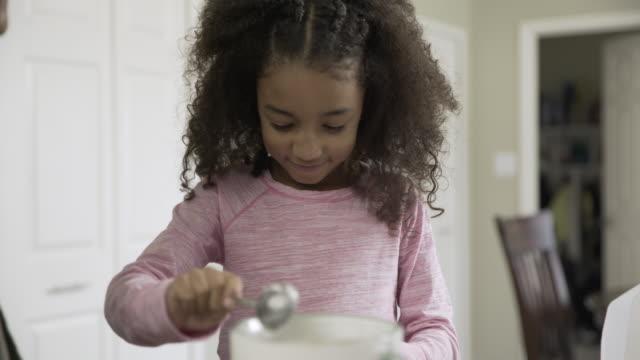 handheld shot of playful girl adding yogurt in blender while preparing smoothie with mother - yoghurt stock videos & royalty-free footage