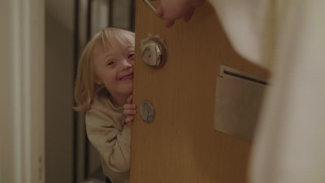 stockvideo's en b-roll-footage met handheld shot of playful girl with differing ability peeking while hiding behind door - minder validen