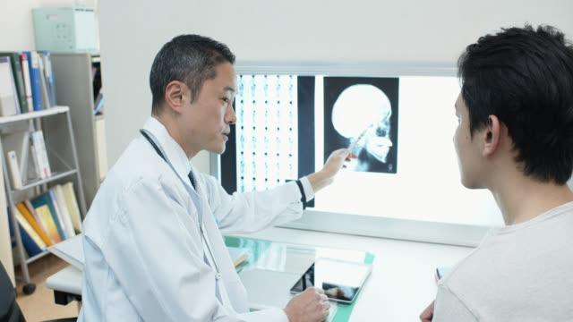 患者に結果を説明する放射線技師のハンドヘルドショット - 健康診断点の映像素材/bロール