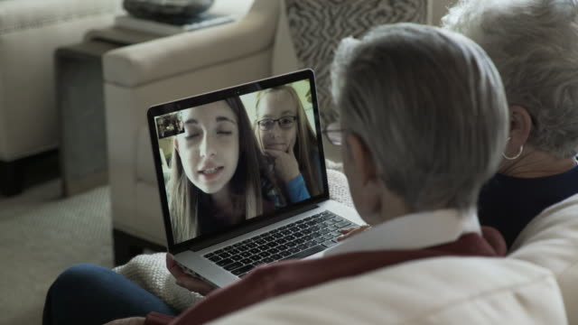 handheld shot of senior couple video conferencing with granddaughters through laptop computer at home - grandfather stock videos & royalty-free footage