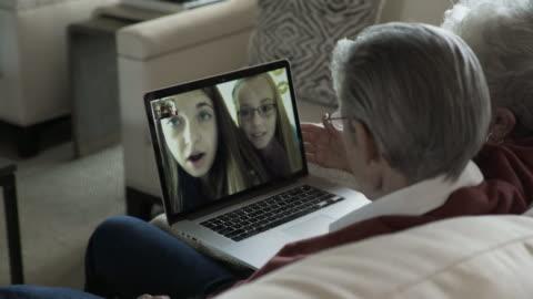 vídeos y material grabado en eventos de stock de handheld shot of senior couple video conferencing with granddaughters through laptop computer at home - nieto