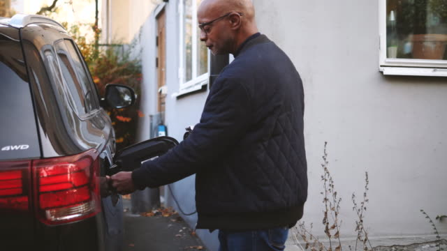 handheld shot of senior man plugging charger in electric car outside house - electric car stock videos & royalty-free footage