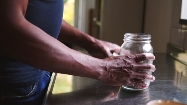 stockvideo's en b-roll-footage met handheld shot of senior man removing dog food from jar and pouring in bowl at kitchen counter - glazen pot