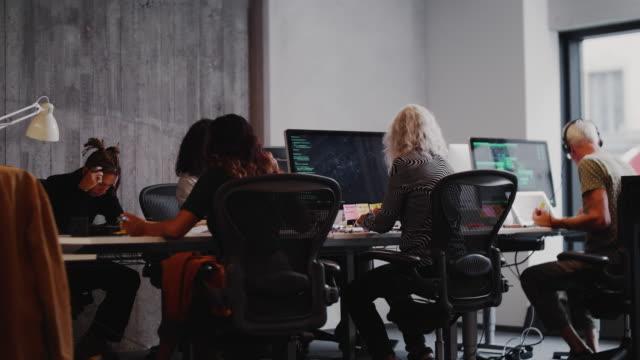 vídeos y material grabado en eventos de stock de handheld shot of senior technicians and colleagues working in creative office - hípster urbano