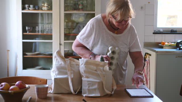 handheld shot of senior woman checking shopping list while removing groceries from bag in kitchen at home - kitchen stock videos & royalty-free footage