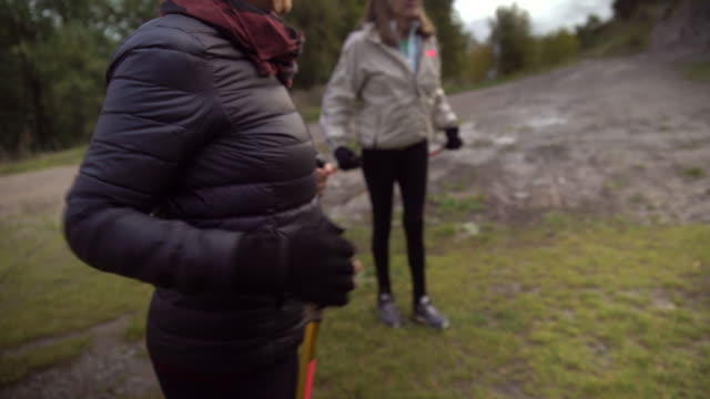 handheld shot of senior woman exercising while standing with friends on grassy field - down jacket stock videos and b-roll footage