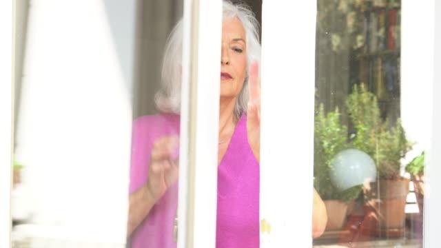 vídeos y material grabado en eventos de stock de handheld shot of senior woman opening window and going outside on balcony - anticipación
