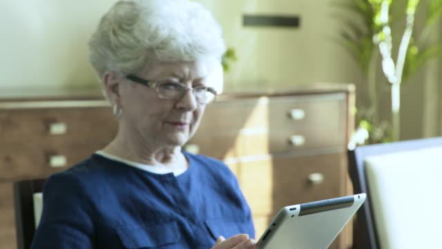 vidéos et rushes de handheld shot of senior woman using tablet computer at home - fondu d'ouverture