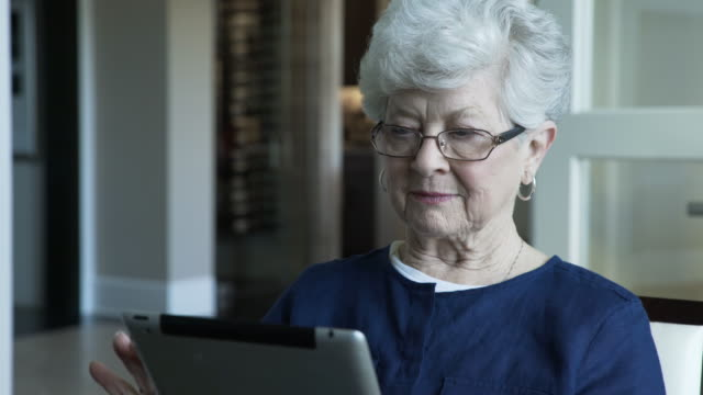 stockvideo's en b-roll-footage met handheld shot of senior woman using tablet computer while sitting at home - oudere internetgebruiker