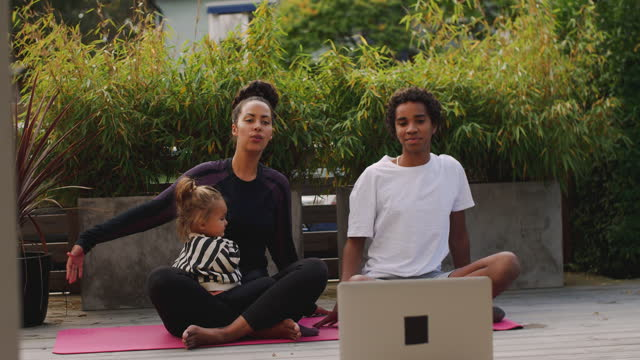 handheld shot of smiling family learning yoga from tutorial through laptop at back yard during pandemic - cross legged stock videos & royalty-free footage