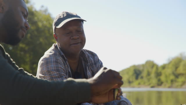 handheld shot of smiling father guiding son in tying fishing bait to rod while sitting on boat at lakeshore - tied up stock videos & royalty-free footage