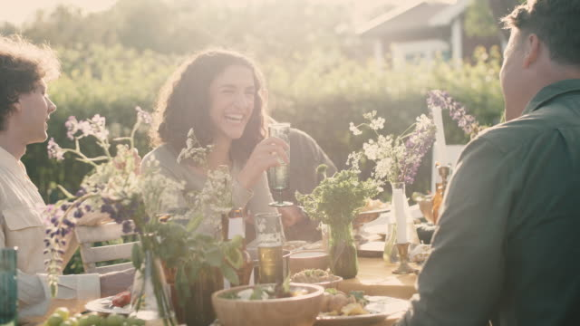 Handheld shot of smiling friends talking at table during garden party