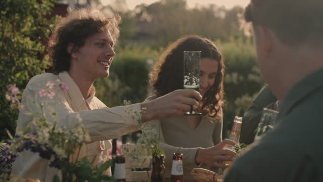 Handheld shot of smiling friends toasting beer bottle during garden party