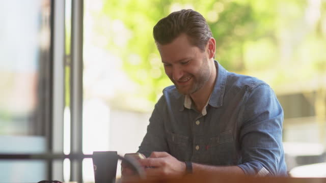 Handheld shot of smiling man using mobile phone while sitting at cafe