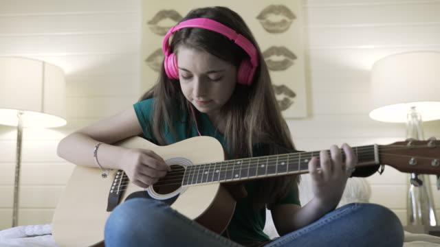 handheld shot of smiling teenage girl playing guitar in bedroom - griffbrett stock-videos und b-roll-filmmaterial