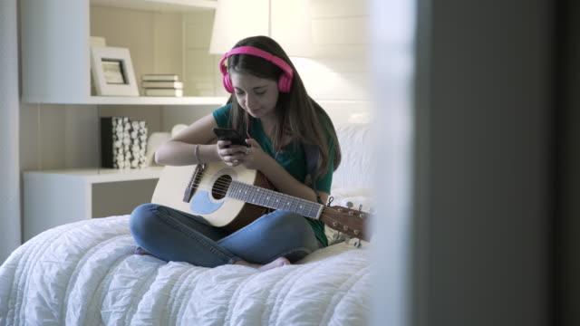 handheld shot of smiling teenage girl using smart phone while sitting with guitar on bed - bedroom doorway stock videos & royalty-free footage