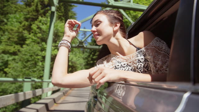 Handheld shot of smiling woman leaning on car window