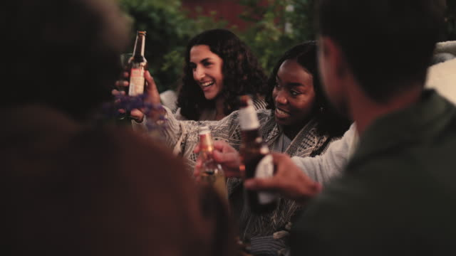 handheld shot of smiling woman talking to friends while toasting during dinner party - 20 29 years stock videos & royalty-free footage