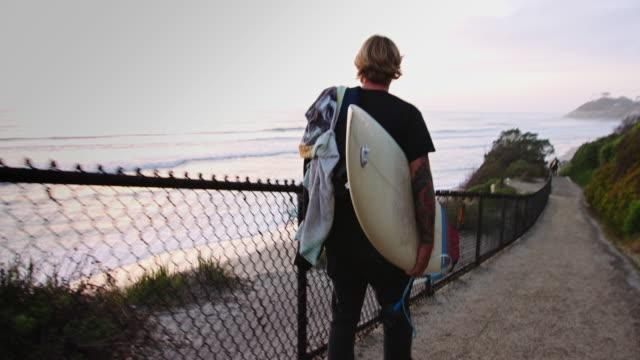 Handheld Shot of Surfer Walking to Beach at Sunset