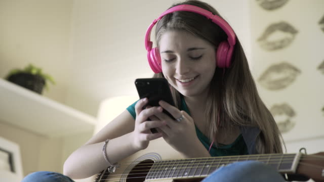 Handheld shot of teenage girl using smart phone while sitting with guitar at home