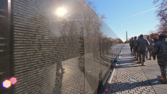A handheld shot of the back of a group of soldiers walking by a wall near the Washington Monument.