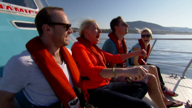 handheld shot of two couples sitting on a charter boat - giacca di salvataggio video stock e b–roll