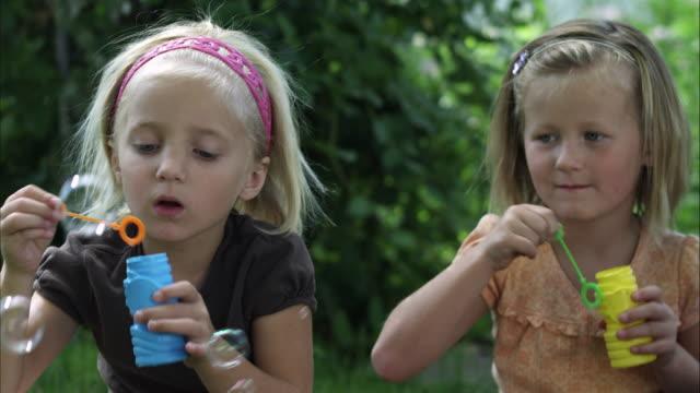 handheld shot of two little girls blowing bubbles - 歐瑞 個影片檔及 b 捲影像