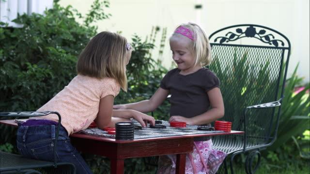 handheld shot of two little girls playing checkers in slow motion - endast flickor bildbanksvideor och videomaterial från bakom kulisserna