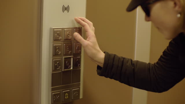 handheld shot of visually impaired woman touching braille on buttons in elevator - braille stock videos & royalty-free footage